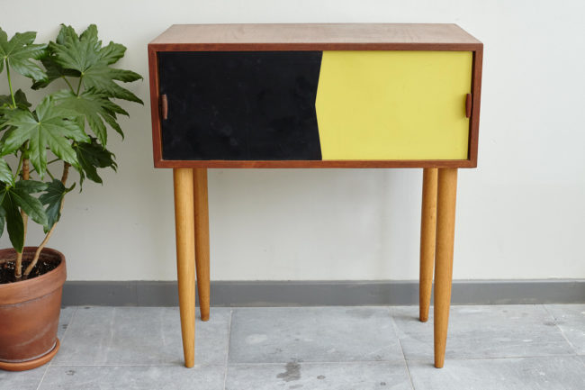 Black and yellow Swedish dresser with plant