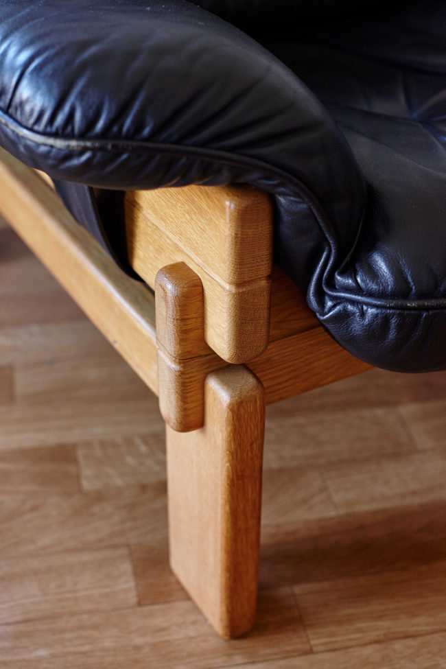 Close up of arm rest of Brazilian armchair in wood and black leather
