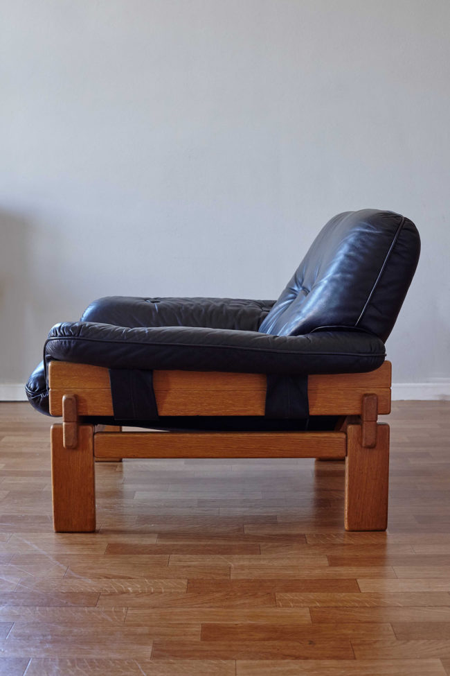 Side view of Brazilian armchair in wood and black leather