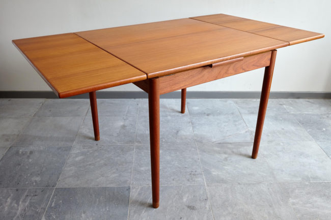 Compact teak dining table with extensions opened